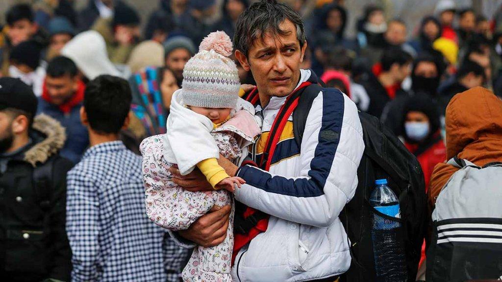 Padre refugiado con su hija en brazo en un campamento improvisado